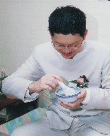 groom in chinese style jacket drinking sweet soup